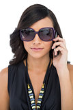 Elegant brunette wearing sunglasses on the phone