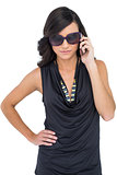 Serious elegant brunette wearing sunglasses on the phone