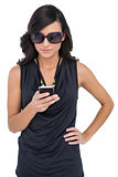 Concentrated elegant brunette wearing sunglasses texting