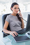 Serious businesswoman answering phone and working on computer