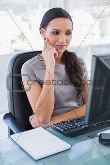 Thoughtful gorgeous businesswoman looking at her computer screen