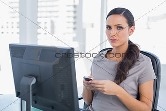 Anxious dark haired businesswoman sending message