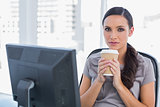 Serious attractive businesswoman holding coffee