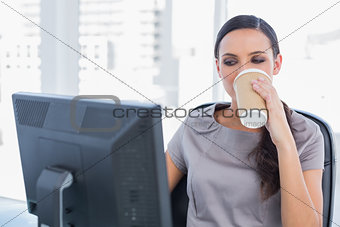 Attractive businesswoman drinking coffee and working
