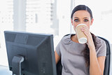 Attractive businesswoman drinking coffee and looking at camera