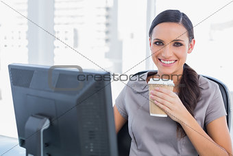 Attractive businesswoman drinking coffee and cheering at camera