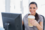 Attractive businesswoman offering coffee to camera