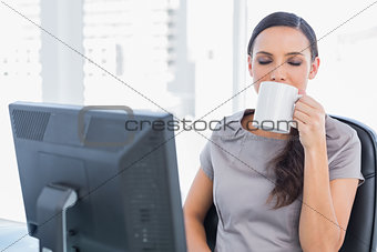 Smiling attractive businesswoman drinking tea