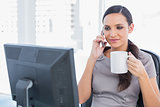 Attractive businesswoman holding coffee and answering phone