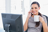 Cheerful attractive businesswoman holding coffee and answering phone