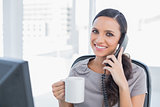 Cheerful secretary answering phone and drinking coffee
