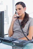 Serious secretary answering land line looking at computer screen