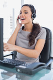 Attractive secretary wearing headset and pointing at computer screen