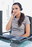 Frowning attractive secretary wearing headset
