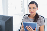 Calm attractive secretary using tablet pc