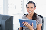 Cheerful attractive secretary using tablet pc