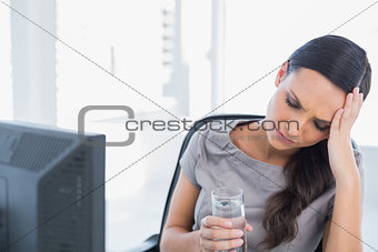 Attractive secretary with headache holding water