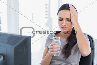 Attractive secretary with headache holding water and touching her head