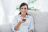 Smiling attractive brunette holding remote