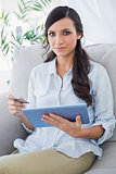 Attractive brunette holding tablet pc and credit card