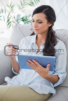 Attractive brunette using her credit card to buy online