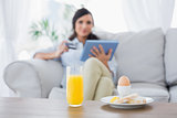 Peaceful brunette having breakfast while buying online