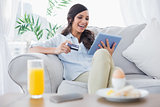 Laughing brunette buying online while having breakfast
