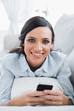 Cheerful pretty woman lying on the couch using her smartphone