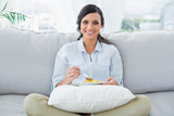 Woman sitting on the couch crossing legs eating fruits