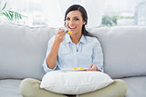 Cheerful woman sitting on the couch crossing legs eating fruits