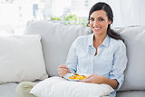Cheerful woman sitting on the sofa eating fruit salad