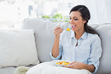 Woman relaxing on the sofa eating fruit salad