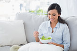 Woman relaxing on the sofa eating salad