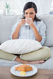 Cute woman on sofa drinking coffee and having croissant