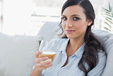 Pretty brunette drinking white wine sitting on sofa