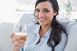 Cheerful pretty brunette drinking white wine sitting on sofa