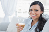 Happy pretty brunette drinking white wine sitting on sofa