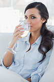 Attractive brunette drinking white wine sitting on sofa