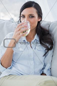 Attractive brunette drinking white wine