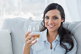 Seductive brunette drinking white wine on sofa