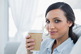 Seductive brunette holding coffee mug