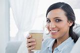 Smiling seductive brunette holding coffee mug