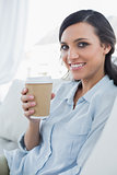 Cheerful seductive brunette holding coffee mug