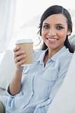 Happy seductive brunette holding coffee mug