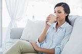 Happy seductive brunette drinking coffee