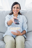 Cheerful pretty brunette watching tv and eating pop corn