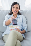Happy pretty brunette watching tv and eating pop corn