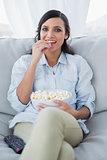Pretty brunette watching tv with pop corn