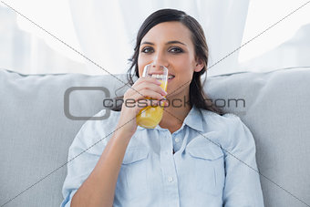 Smiling brunette drinking orange juice