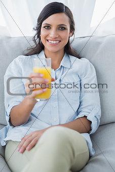 Smiling brunette offering orange juice to camera